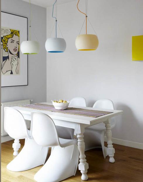 """Cadeiras Panton brancas com mesa de estilo para """"quebrar"""", As três luminárias em cores diferentes e a gravura de história em quadrinhos  deixam a sala """"especial"""""""