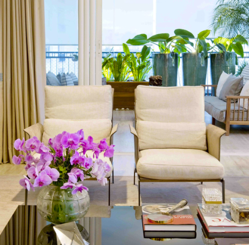 """Neste projeto da arquiteta Zize Zink , os vasos bem simétricos na varanda criam um """"fundo"""" para a sala."""