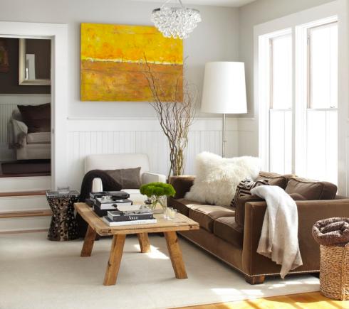Almofadas de pele e mantas de lã sobre o sofá.