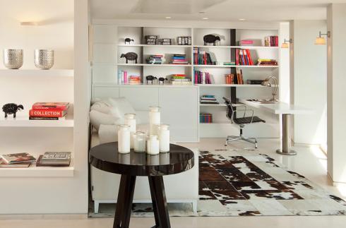 Em uma estante branca, o bacana é que ela some e dá destaque para os objetos e livros coloridos.